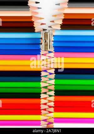 Set of pastel colored pencils and a sharpener forming a zipper - Stock Photo