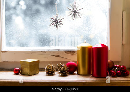 red and golden christmas decoration, indoors in front of a window - Stock Photo