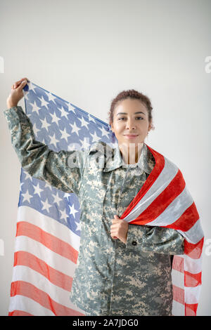 Patriotic young pretty servicewoman holding national flag - Stock Photo