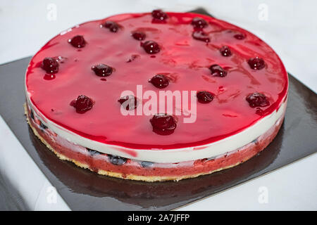 Delicious red cake with cherries on top - Stock Photo