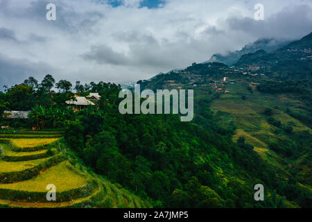 Top aerial birdseye view of harvested green rice terraces and small shacks in Sapa, North Vietnam. Shot in Autumn, October 2019 - Stock Photo
