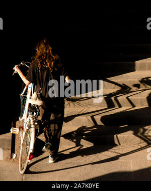 One teenage girl in black pushing the white bike up the public stairs in sunlight and shadows, from behind - Stock Photo