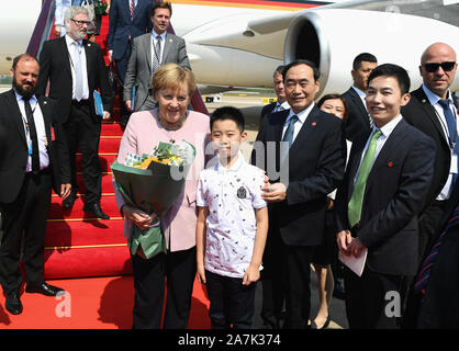 German chancellor Angela Merkel, pink, takes picture with a child who presents her a bouque in Wuhan city, central China's Hubei province, 7 September - Stock Photo