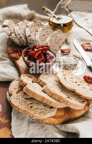 Healthy rye wholegrain bread with olives, avocado and sun-dried tomatoes on a wooden farmer's table. Homemade cake. traditional Italian food. - Stock Photo