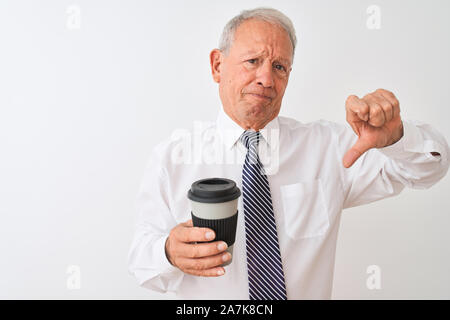 Senior grey-haired businessman drinking take away coffee over isolated white background with angry face, negative sign showing dislike with thumbs dow - Stock Photo