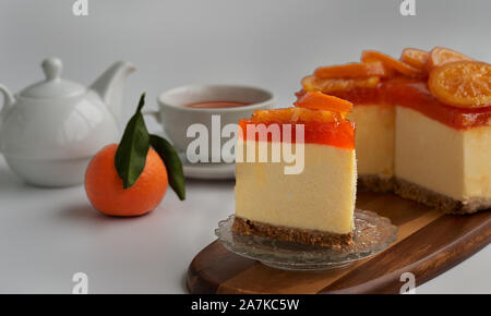 Front view of a piece of candied orange cake with the rest of the pie, a fresh orange, a teapot and a cup of tea in soft-focus in the background - Stock Photo