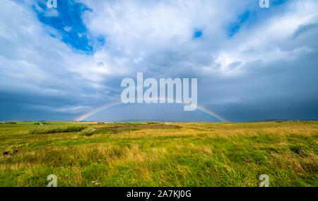 Rainbow after a storm on the grass fields of the mainland, Orkney, Scotland - Stock Photo