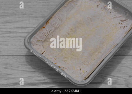 Frozen beef lasagne, or lasagna, in a plastic tray packaging. Frozen ready meal on a grey wood background - Stock Photo