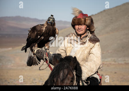 Portrait of a traditional kazakh eagle hunter with his golden eagle on horseback. Ulgii, Mongolia. - Stock Photo