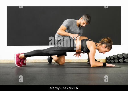 Woman in gym doing plank exercise with the help of a professional personal trainer, viewed from the side from the floor level - Stock Photo