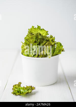Kale Chips with salt in paper cup. Homemade healthy snack for low carb, keto, low calorie diet. White wooden background. Ready-to-eat kale chips, copy space for text. Vertical - Stock Photo