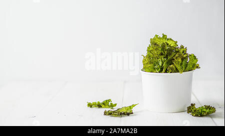 Kale Chips with salt in paper cup. Homemade healthy snack for low carb, keto, low calorie diet. White wooden background. Ready-to-eat kale chips, copy space for text. Banner - Stock Photo