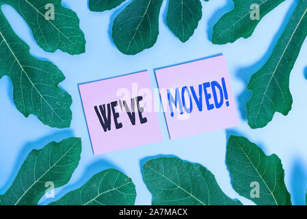 Text sign showing We Ve Moved. Business photo text To go from one residence or location to another Relocate Leaves surrounding notepaper above an empt - Stock Photo