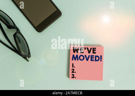 Text sign showing We Ve Moved. Business photo showcasing To go from one residence or location to another Relocate Dark eyeglasses colored sticky note - Stock Photo