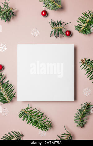 Blank paper greeting or invitation card on pink background with fir tree branches, red berries and glitter confetti stars. Christmas, New Year, winter - Stock Photo