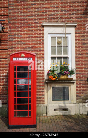 Iconic red British telephone box in front of a brick building with window and flower box on a bright, sunny day