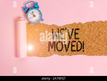 Text sign showing We Ve Moved. Business photo showcasing To go from one residence or location to another Relocate Alarm clock and torn cardboard place - Stock Photo
