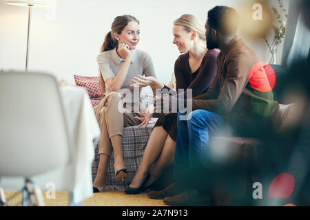 Full length view at group of modern young people chatting while sitting on cozy sofa at Christmas party, copy space