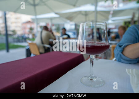 Glass of red sangria in wine glass on table at outdoor restaurant - Stock Photo