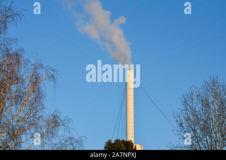 Industrial smoking  pipe emitting  smoke from factory against blue sky.Environmental pollution. - Stock Photo