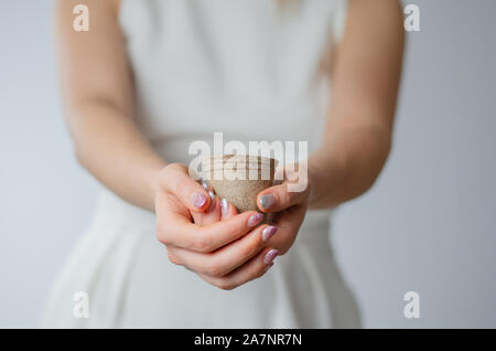 Close-up of woman hands holding an empty paper cup.