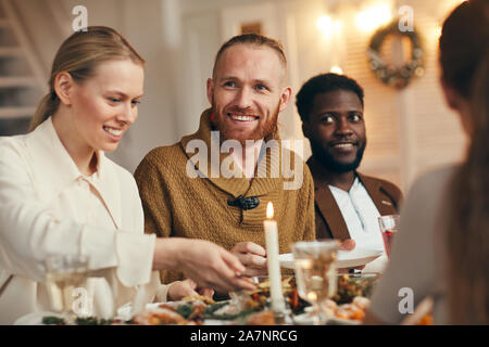 Portrait of contemporary bearded man smiling happily while celebrating Christmas with friends and family at dinner table