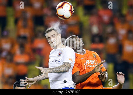 Brazilian football player Roger Krug Guedes, known as Roger Guedes, left, of Shandong Luneng Taishan heads the ball against Cameroonian football playe - Stock Photo