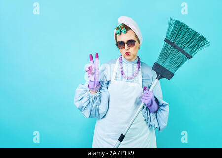 Cleaning Lady Fun. Elderly funny housewife fooling around with a broom. Full body isolated blue. Comical cleaning lady, old woman funky - Stock Photo