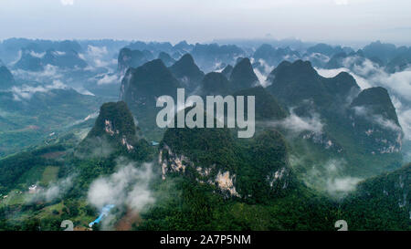 The mountains and hills are surrounded by mist and cloud along the Li River at sunrise in Yangshuo county, Guilin city, south China's Guangxi Zhuang A - Stock Photo