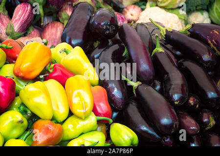 Group of eggplants and sweet red and green peppers background - Stock Photo
