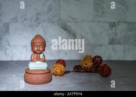 Monk sitting down praying statue home decoration ornament in spotlight casting shadow. Rattan cane balls, praying beads. Empty copy space for text. Ma - Stock Photo