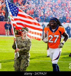 November 03, 2019: Denver Broncos cornerback Davontae Harris (27) runs on the field accompanied by a U.S. Armed Forces member before the game between Denver and Cleveland at Empower Field in Denver, CO. Denver hung on to win 24-19 to improve to 3-6. Derek Regensburger/CSM. - Stock Photo
