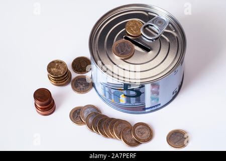 The concept of money. A piggy bank in the form of a tin can and, next to the piggy bank, money bills and coins are laid out.Financial risk and safety - Stock Photo