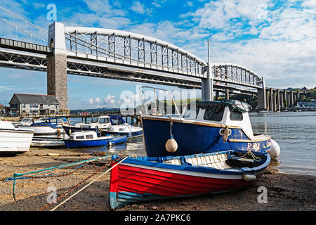 fishing boats by the river tamar in saltash cornwall, the famous royal albert bridge designed by isambard kingdom brunel in the background - Stock Photo