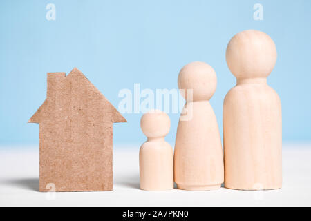 Wooden figures family with cardboard cutout house on blue background. Concept of moving to new home, settlement, rental, mortgage, eviction. - Stock Photo