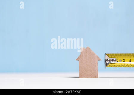 Metal measuring tape and cardboard cutout house on blue background with copy space. Concept of surveying, budgeting, repairing. - Stock Photo