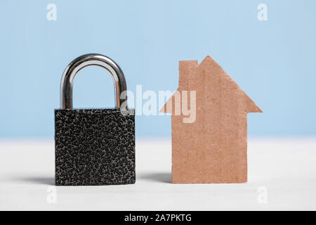 Cardboard cutout house and black padlock on blue and white background. Concept of security of real estate, new home, apartment alarm system. - Stock Photo