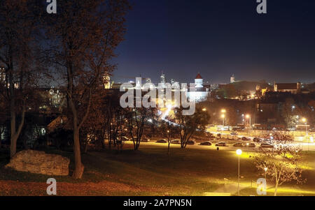 Vilnius city illuminated at night with Gediminas tower, three crosses and Church of the Holy Mother of God from bastion hill - Stock Photo