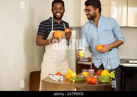 Two male students in casual clothes going to cooking smoothie standing in kitchen of hostel, holding grapefruit, orange, apple, tomato in hands, cheer - Stock Photo