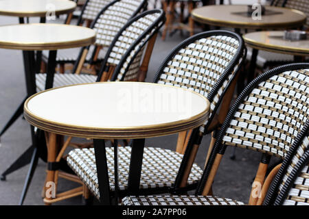 Paris, France. Cafe Terrace Table with Wicker Chairs. Classic French Cafe View. - Stock Photo