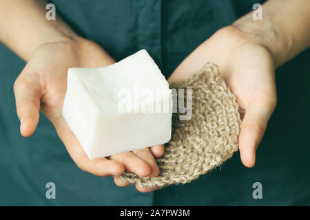 Eco-friendly cleaning kit. Organic soap and jute washcloth in the woman's hand. Zero waste concept, plastic-free, eco-friendly shopping, vegan - Stock Photo