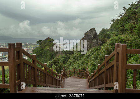 wooden staircase at Seongsan Ilchulbong on Jeju island on gloomy day - Stock Photo