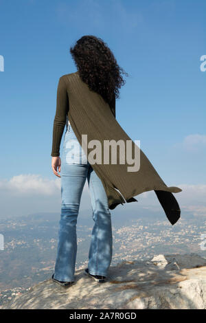 Rear view of young woman standing outdoors - Stock Photo