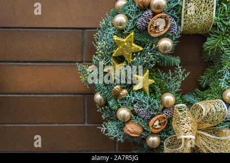 Handmade Christmas wreath from fresh fir tree branches decorated with golden ornaments stars baubles walnuts ribbon hanging on brown brick house wall. - Stock Photo