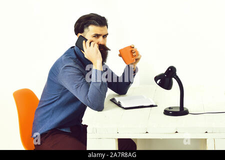 Bearded man, long beard. Brutal caucasian unshaven serious hipster with moustache talking by cell phone and orange mug at white vintage wooden table isolated on white background - Stock Photo