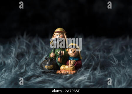 the holy family, the child jesus, the virgin mary and saint joseph, on a gray artificial fur, against a dark background - Stock Photo