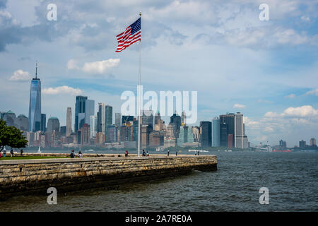 New York, USA - June 7, 2019:   American flag on Liberty Island in New York Harbor and Manhattan skyline