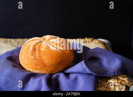 Ready-to-eat, fresh loaf on rustic stand holded in a blue napkin. - Stock Photo