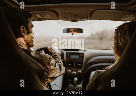 Beautiful couple doing a car trip on countryroad, view from rear seat. - Stock Photo