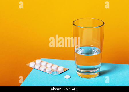 Aspirin pills and a glass of water on the table. Treatment of cold - Stock Photo